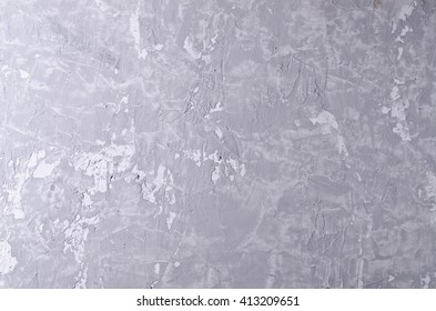 Gray concrete background with cracks and irregularities. Selective focus.