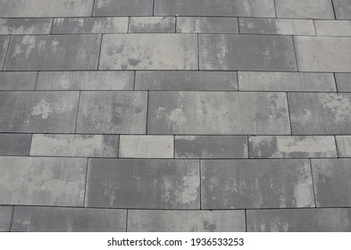 gray concrete paving gray with stains in the appearance of old stone, or fired paving in several formats stacked into the surface of the square