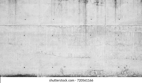Gray concrete wall with dark wet stains, frontal background photo texture