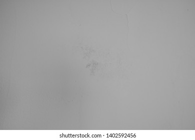 Gray concrete wall with plastered structures and soiling in industrial design. Pastel-colored stone wall with as background and design element for artful collagen.