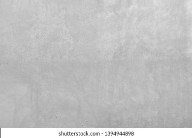 Gray concrete wall with rough surface. Stone wall with light structure of wear. Large wall made of cement in industrial design style