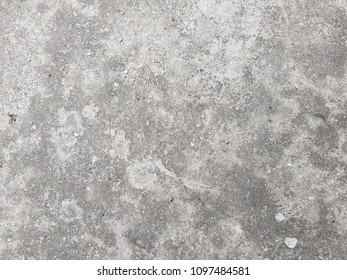 Gray concrete wall with white abrasion and small holes.