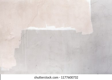Gray concrete wall with white and pink paint layers, close-up background texture