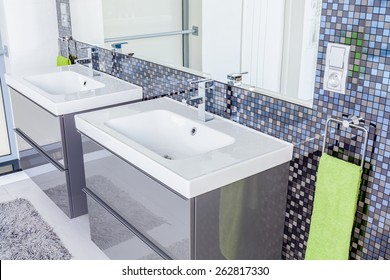 Gray contemporary toilet design with two washbasins