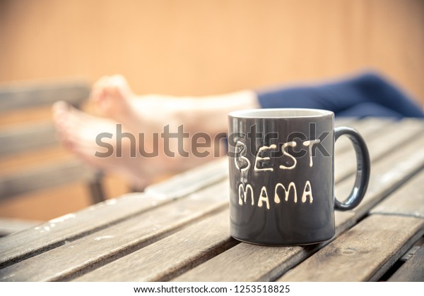 Gray cup that celebrates Mother's Day, the feet of women who relax in the background, the terrace and the garden furniture.