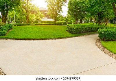 Gray curve pattern walkway, sand washed finishing on concrete paving, brown gravel on border, a smooth green grass lawn, trees with supporting and shrub in garden, good maintenance park