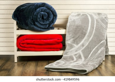 Gray, Dark Blue, Red winter Blankets on wooden shelf unit