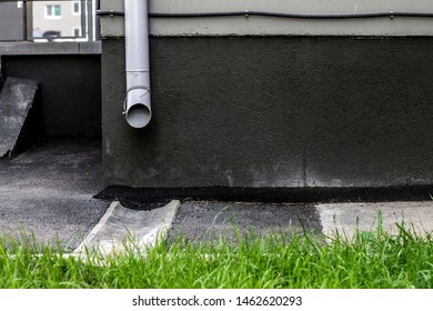gray drain pipe on the facade of the building and in front of the lawn