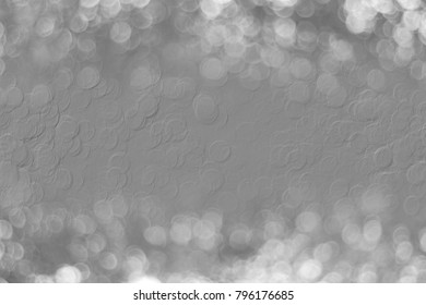 Gray embossed abstract texture of a cement wall blends together in the center of a gray bokeh background.