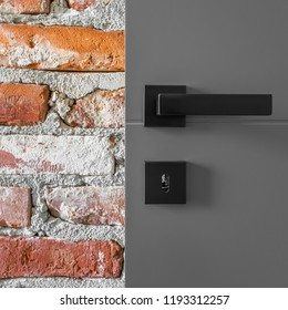 Gray entry door with black handle and industrial brick wall, close up