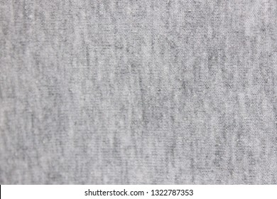 Gray fabric texture background of light material design. Bright grey white cloth pattern of hoodie, sweater, pullover or shirt, casual clothing. Close up top view of grey backdrop with empty copyspace