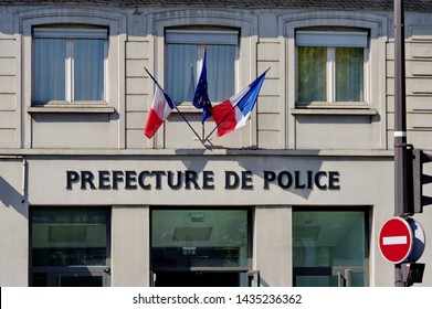 Gray facade of the police headquarters whit french flags. French text: Préfecture de Police.  Paris. France.