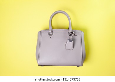 gray female bag on a yellow background. view from above. copy space