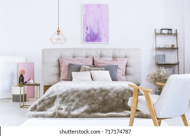 Gray fur duvet covering a king-size bed with beige bedhead in chic bedroom for a modern woman