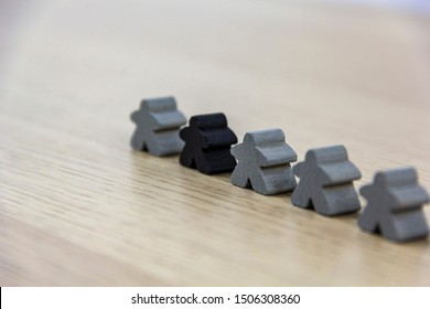 Gray gaming pieces and a black meeple, diversity concept