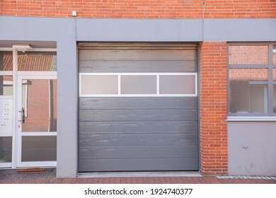 Gray garage door on a building. Automatic hall gate.