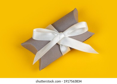 Gray gift box with silver ribbon on yellow background.