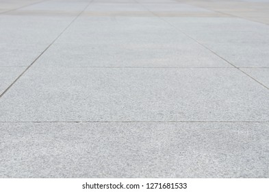 Gray granite paving slab. Photo with perspective. Selective focus. A large pattern of sidewalk tiles for pedestrians.