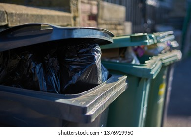 Gray and green garbage cans overfilled with domestic refuse