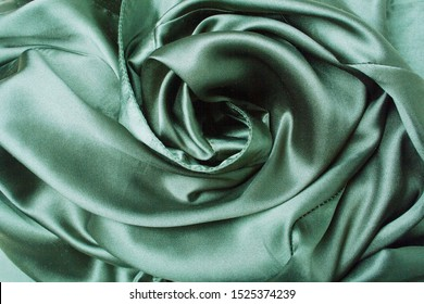 Gray green satin fabric background. Emerald background top view