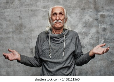 Gray haired Caucasian grandfather with a blank face spreads his arms to the side on a gray background in the studio