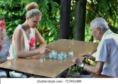 Gray haired grandfather playing chess with his granddaughter. Concept of active elderly people during retirement. Everyday joy lifestyle without age limitation.