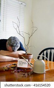 Gray haired man with his head down behind a dead plant and his wife's note to water the plant.