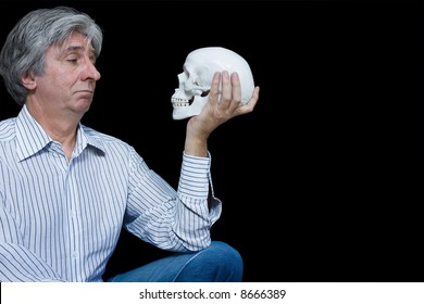 Gray haired man staring at a skull