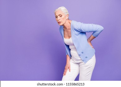 Gray haired old beautiful  woman wearing casual suffering from back pain. Empty blank copy space. Isolated over violet pastel background
