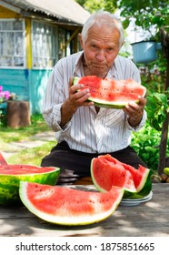 gray haired old man eating a huge ripe watermelon near the village house