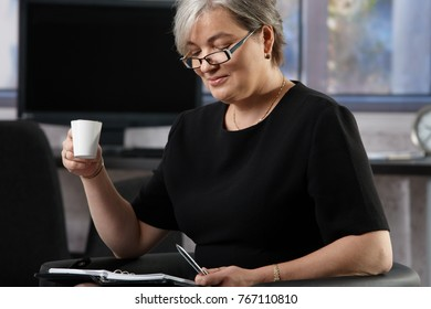 Gray haired senior businesswoman drinking coffee in office.