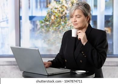 Gray haired senior businesswoman working with laptop drinking coffee in office.