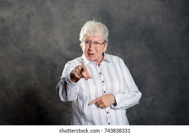 gray hairy elderly woman looking angry and pointing in to the camera