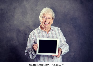 gray hairy elderly woman showing tablet pc and smiling