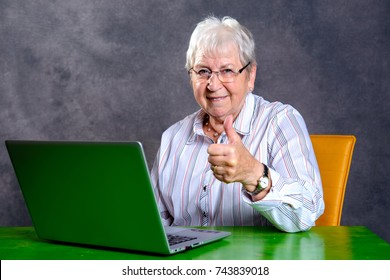 gray hairy elderly woman with thumb up using pc and smiling