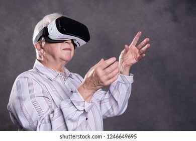 gray hairy elderly woman using virtual reality glasses and looking surprised