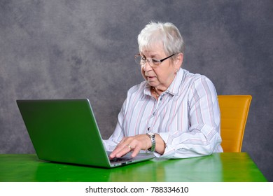 gray hairy elderly woman using laptop on table