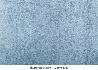 Gray hotel towel wave texture or material close up. New terry cotton towels or soft washcloth background with waves and folds flat lay and top view