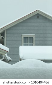 A gray house with a window in a white frame is almost covered with snow. Snow collapse, Larvik, Norway.