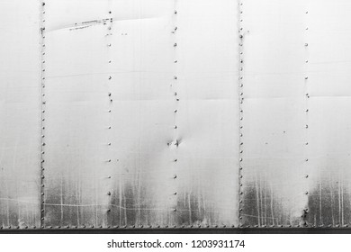 Gray industrial metal wall with rivets pattern. Background photo texture, front view