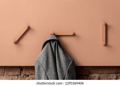 Gray jacket is hanging on the metal coral hanger between other hangers on the same color textured panel on the brick wall background indoors. Closeup horizontal photo.