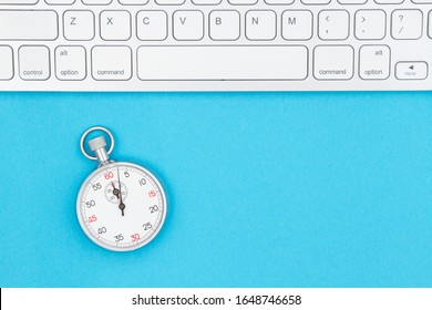 Gray keyboard with a stopwatch with blue background with copy space