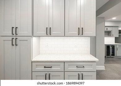 Gray kitchen built with shaker style cabinets and white quartz countertop. Shows stainless steel appliances, white brick subway tile back splash and  under cabinet lights.