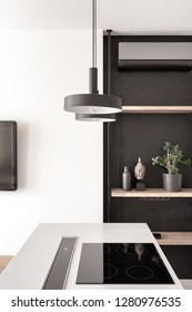 Gray kitchen island with a cooking surface on the white wall background in the modern interior. There are hanging dark lamps, wooden shelves with a plant, vase, statuette, TV on the wall, conditioner.