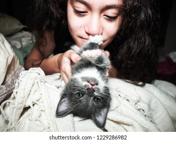 A gray kitten and a girl playing on the bed. The kitten looks at the camera upside-down one paw on the girl's mouth and the other paw reaching to the camera.