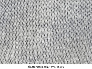 Gray knitted carpet closeup. Textile texture grey color, detailed warm yarn background. Natural woolen fabric, sweater fragment.