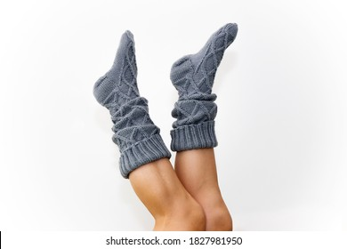 Gray knitted knee socks on the legs on a white background. Legs in long socks upside down. A beautiful knitted product for a gift. We knit with our own hands. Hobby