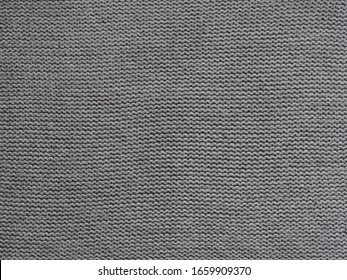 Gray knitted textured background, knit with purl loops. Hand knitting with woolen yarn.
