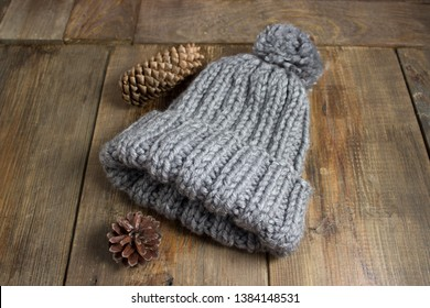 Gray, knitted, winter, warm, soft handmade hat with a fir cone, on a brown background.