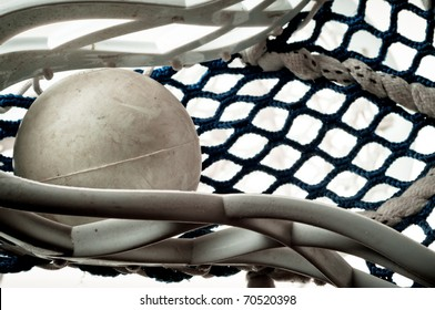 Gray lacrosse ball held in the head with blue netting